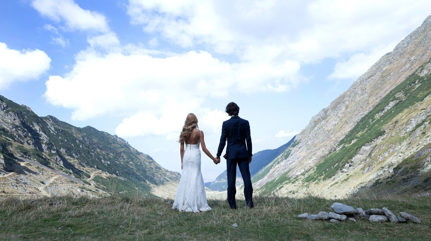 Mountain Wedding | Sky full of love | Bride and Groom holding hands looking over a valley between two steep cliffsides
